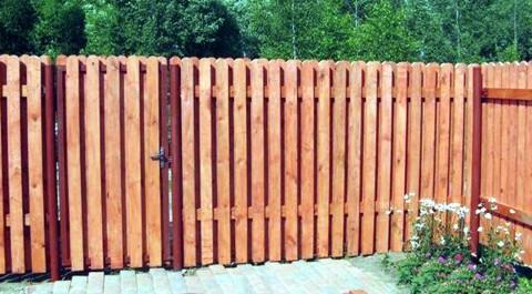 деревянный забор из досок с прозорами  - фото