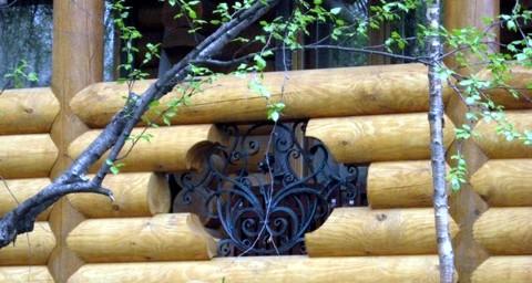 бревенчатый забор с декором из ковки - фото