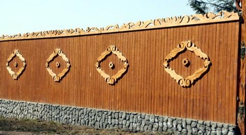 деревянный забор из досок с элементами декора - фото